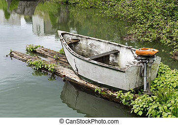 Skiff with outboard motor - Abandoned skiff with rusty...