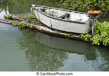 Small skiff with vintage motor - A small abandoned skiff...
