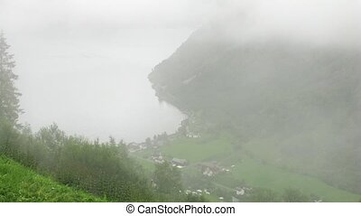 Little Norwegian village covered in fog, top-down view, time...