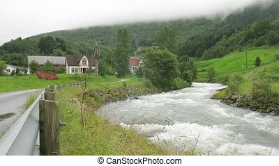 Swift river flow through little village in mountains, time...