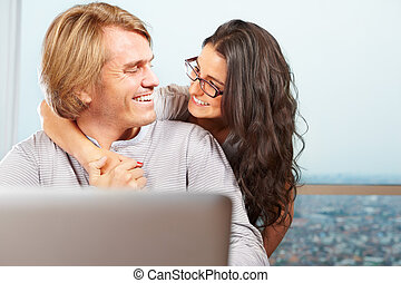 Happy couple in front of laptop