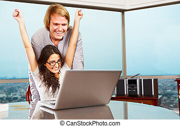 Happy couple in front of laptop - Successful lady expressing...