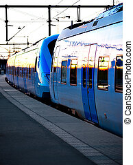 Blue commuter train in evening light at station
