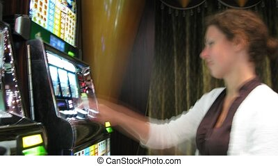 woman sitting at slot machine in casino, time lapse - Young...