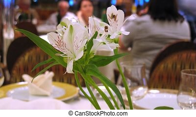 White orchid on table in restaurant, time lapse