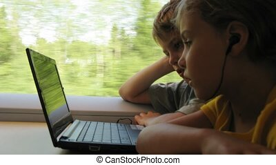 Boy and girl go in train and use laptop near a window, time...