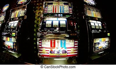 Number of slot machines, man presses button on slot machine...