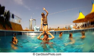 Boy stays on shoulders of father in pool, then boy jumps.