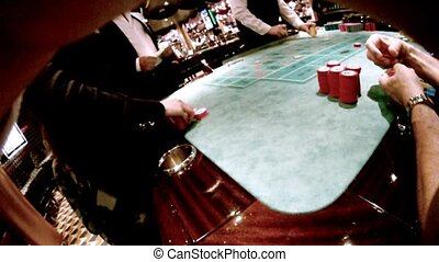 Casino craps table, people sit at table with chips,...