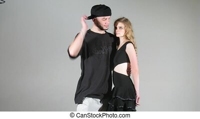Young woman and guy pose for photographer in studio