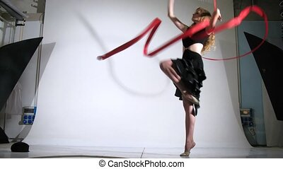 Girl gymnast with ribbon poses for photographer in studio -...