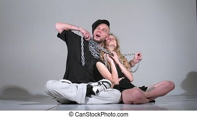 woman and guy and with  chain pose for photographer in studio