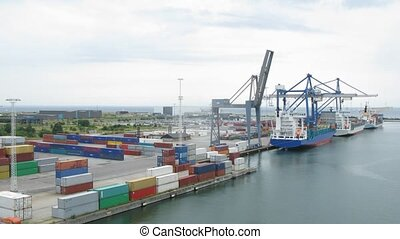 Three big freight ships being loaded with containers,...