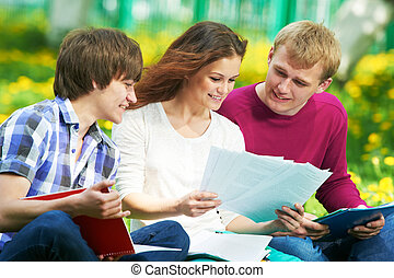 Three smiling young students outdoors