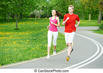 Young man and woman jogging outdoors - Young fitness man and...