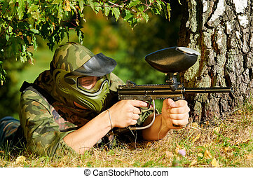 paintball player aiming with marker - paintball sport player...