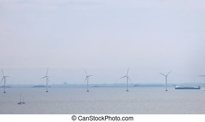 Wind farms stationed on water in front of Copenhagen, time lapse