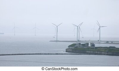 Ships pass between wind farms in gloomy weather, time lapse