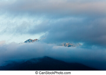 Dark sunset clouds over high rugged mountain peaks