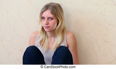 girl sits leaning against wall and looks toward - Young girl...