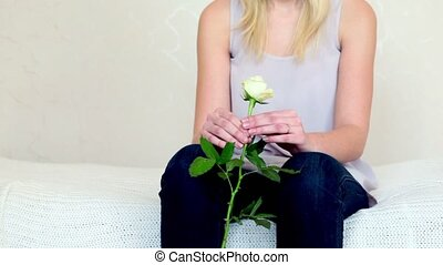 Hands of girl holds rose and sit on bed