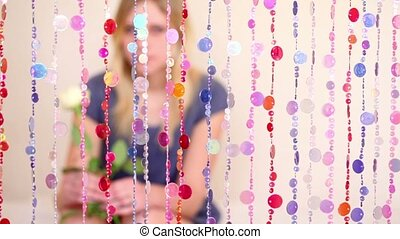 Girl sit behind beads curtain, blurred - Girl sit behind...