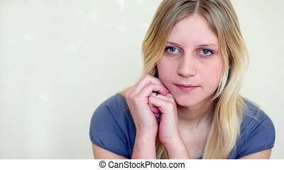 Girl sits with head propped by hands and stares, her face is...