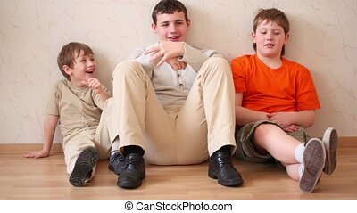 Three boys sit, looks forth and talk - Three boys sit...