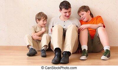 Three boys sit on floor and read magazine