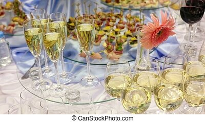 Hand take glass of champagne from appetizer table with...