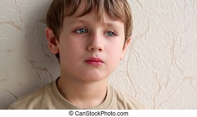 little boy face on background of wall covered with...
