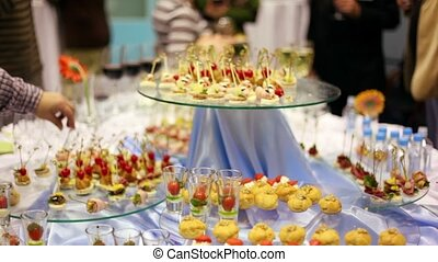Hands take canapes from appetizer table with wine and other...