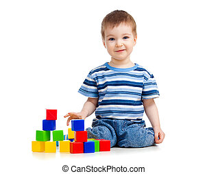 kid playing toy blocks and looking to camera