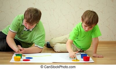 Two boys sit and draw ink on paper using their fingers - Two...