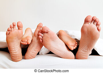 feet of a family in bed under the covers.