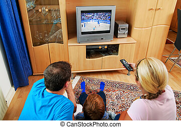 family watching television - a family watching tv with tv