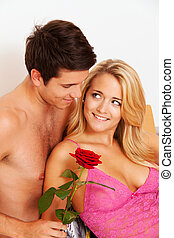 romantic couple in bed with rose.