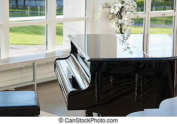 Grand piano in the hall shined by the sun
