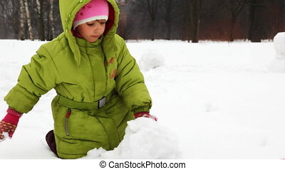 girl play with snow and make snowman - cute little girl play...