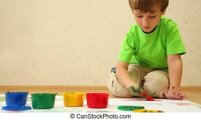 Boy draws color paints with his fingers on sheet of paper -...