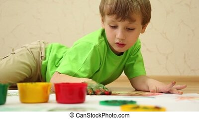 Boy lay on floor and draws color paints with his palm