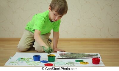 Boy draws color paints and makes handprints on sheet of...