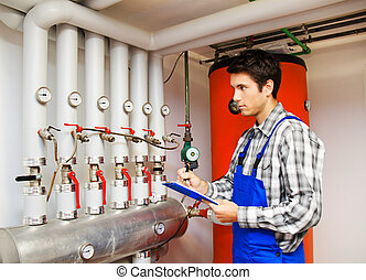 heating engineer in the boiler room - young heating...