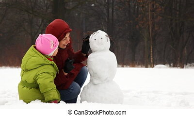 mother with cute little daughter make face of snowman in...