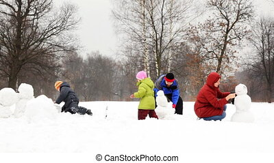 mother and father with two children make snowman, part3 -...