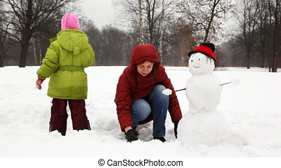 mother with cute little daughter near ready snowman