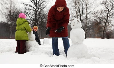 mother make hands for snowman with two children in winter