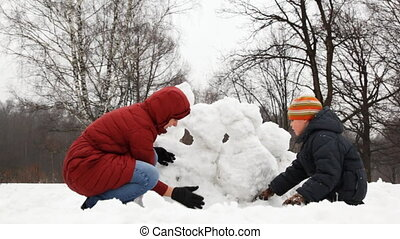 mother with little son make snow fortress