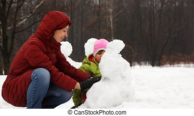 mother with cute little daughter make snowman in winter