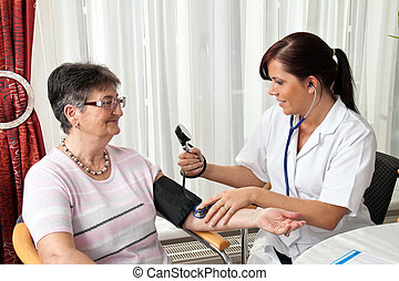 doctor patient attaches the blood pressure - a young doctor...